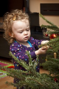 Little child decorating christmas tree